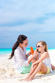 istock Young mother applying sun cream to daughter nose on the beach. The concept of protection from ultraviolet radiation 686753378