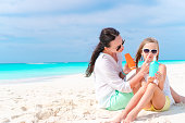 istock Young mother applying sun cream to daughter nose on the beach. The concept of protection from ultraviolet radiation 686758922