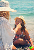 istock Young Mother Applying Suntan Lotion On Daughter's Face 665946058