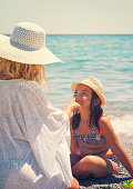 istock Young Mother Applying Suntan Lotion On Daughter's Face 665946444