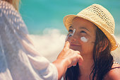 istock Young Mother Applying Suntan Lotion On Daughter's Face 665946478