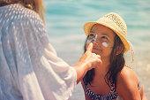 若い母親は、娘の顔に適用する日焼け止めローション