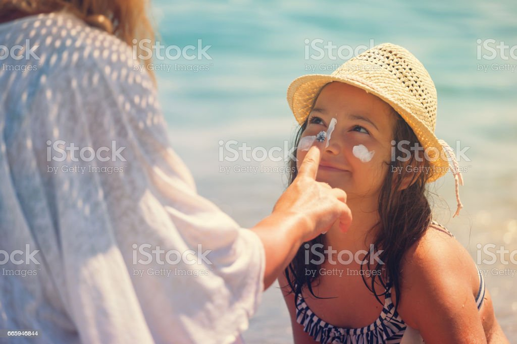 Young Mother Applying Suntan Lotion On Daughter's Face stock photo