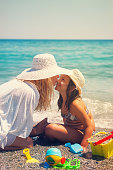 istock Young Mother Applying Suntan Lotion On Daughter's Face 665946902