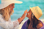 istock Young Mother Applying Suntan Lotion On Daughter's Face 680737468