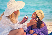 istock Young Mother Applying Suntan Lotion On Daughter's Face 680737716