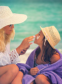 istock Young Mother Applying Suntan Lotion On Daughter's Face 680737778