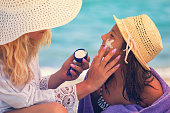 istock Young Mother Applying Suntan Lotion On Daughter's Face 680737812
