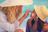 istock Young Mother Applying Suntan Lotion On Daughter's Face 680737858