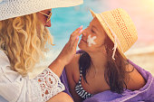 istock Young Mother Applying Suntan Lotion On Daughter's Face 689798660