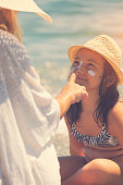 istock Young Mother Applying Suntan Lotion On Daughter's Face 958480006