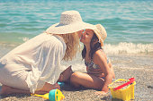 istock Young Mother Applying Suntan Lotion On Daughter's Face 958480040