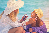 istock Young Mother Applying Suntan Lotion On Daughter's Face 958919012