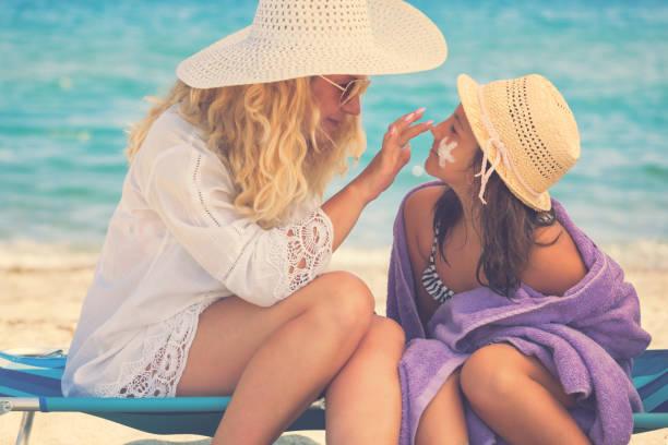 Junge Mutter mit Sonnencreme auf Tochter Gesicht – Foto