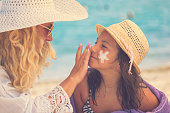 istock Young Mother Applying Suntan Lotion On Daughter's Face 958919072