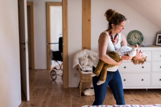 junge mutter zu hause halten ihren niedlichen kleinen sohn - mutterkleiderschrank stock-fotos und bilder