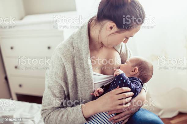 Young Mother Breastfed Her Baby Girl Mother Breastfed Baby At The Bedroom - Fotografias de stock e mais imagens de Abraçar