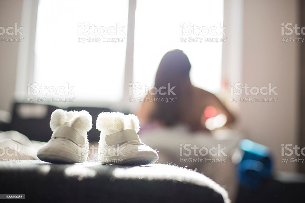 Young mother breastfeeding baby, baby shoes in focus royalty-free stock photo