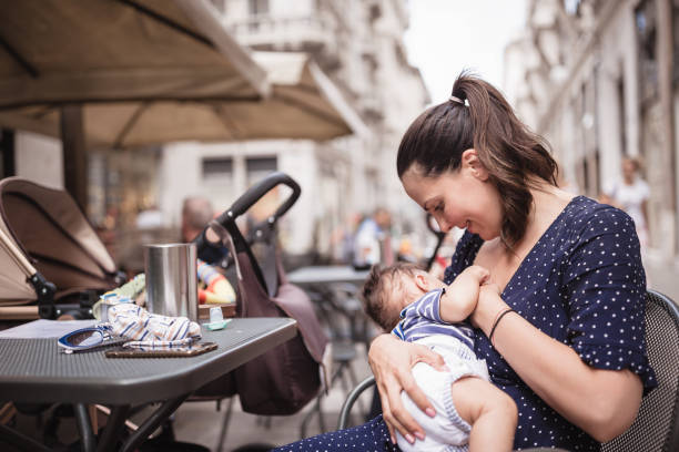 Young mother breastfeeding her baby boy in public place stock photo