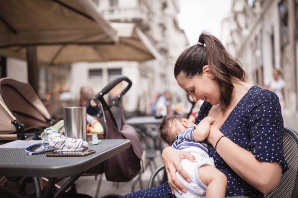 Junge Mutter stillt ihren kleinen Jungen an öffentlichen Orten – Foto