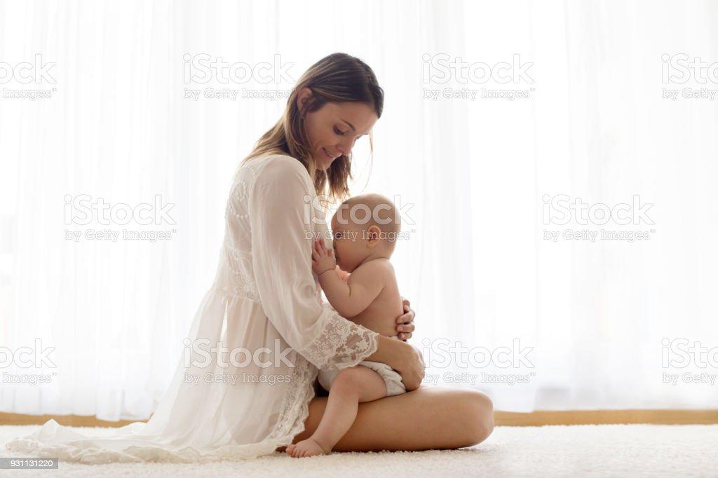Joven madre amamantando su bebé recién nacido en casa - foto de stock