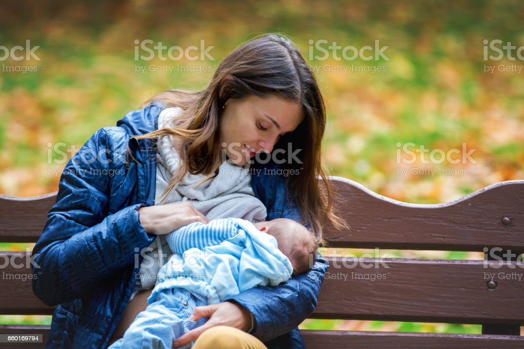 Young mother, breastfeeding her newborn baby boy outdoor in the park stock photo