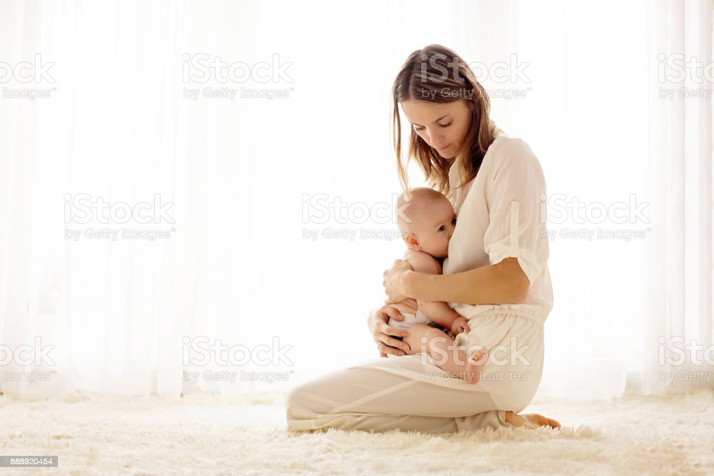 Young mother breastfeeding her newborn baby boy stock photo