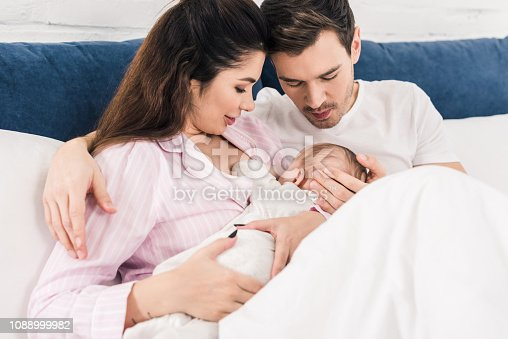young mother breastfeeding little baby with husband near by on bed at home