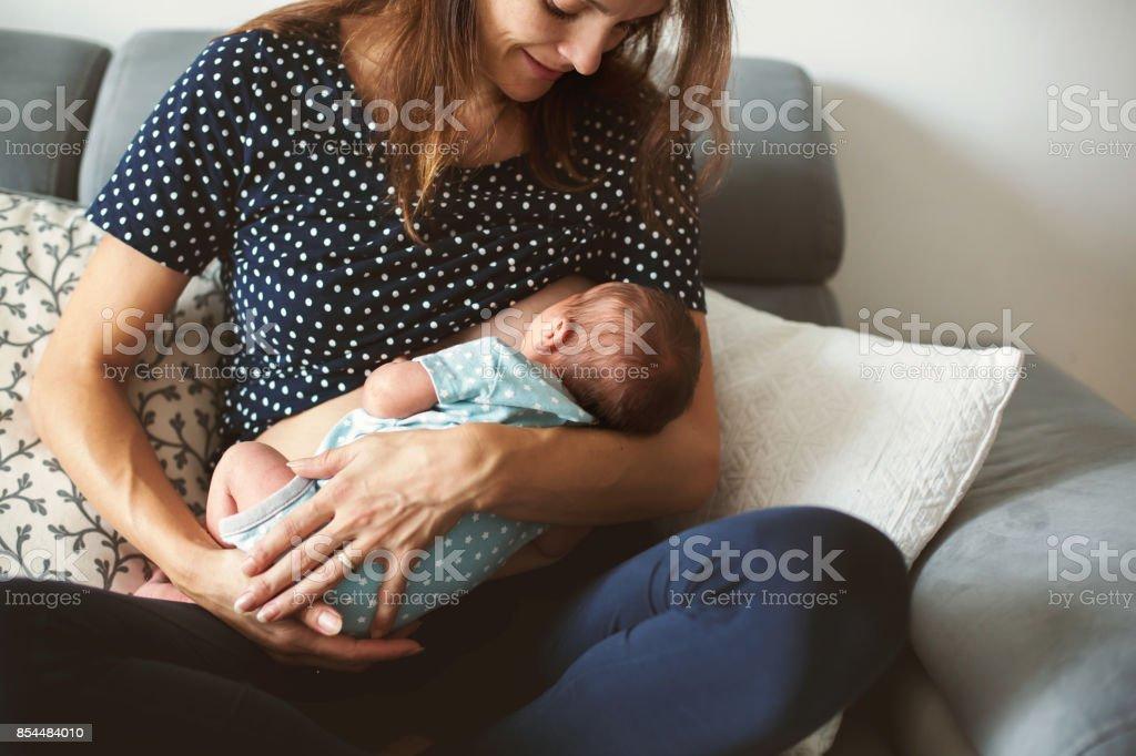 Joven madre amamanta su bebé, sosteniéndolo en sus brazos - foto de stock