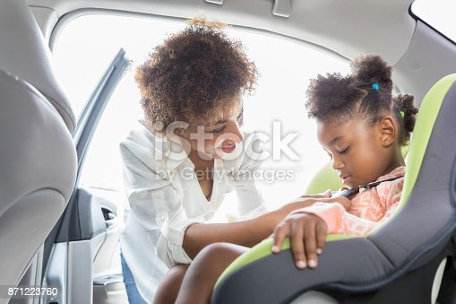 istock Young mother buckles preschooler into car seat 871223760