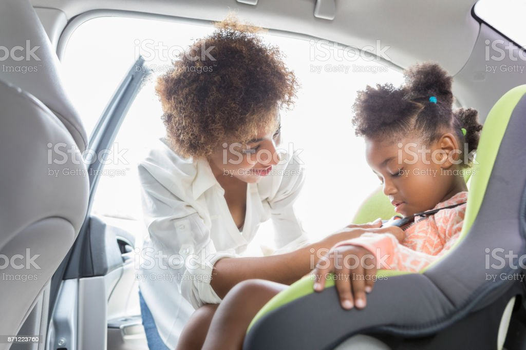 Young mother buckles preschooler into car seat stock photo