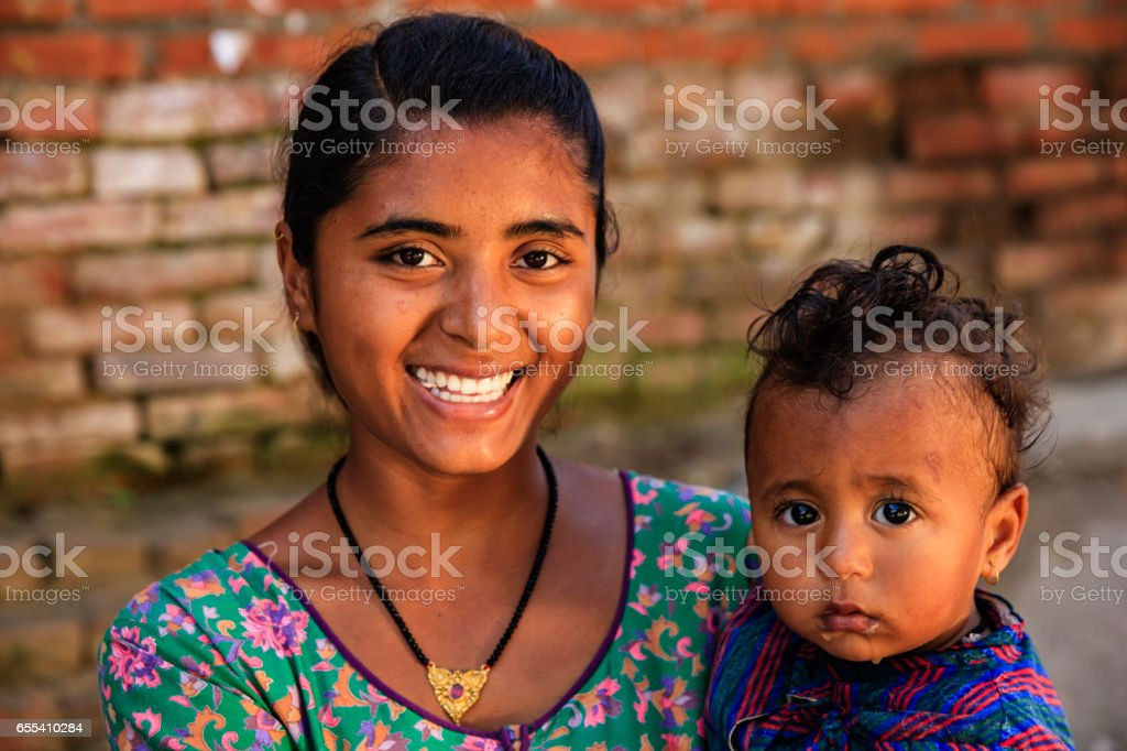 Young mother carrying her baby, Bhaktapur, Nepal stock photo