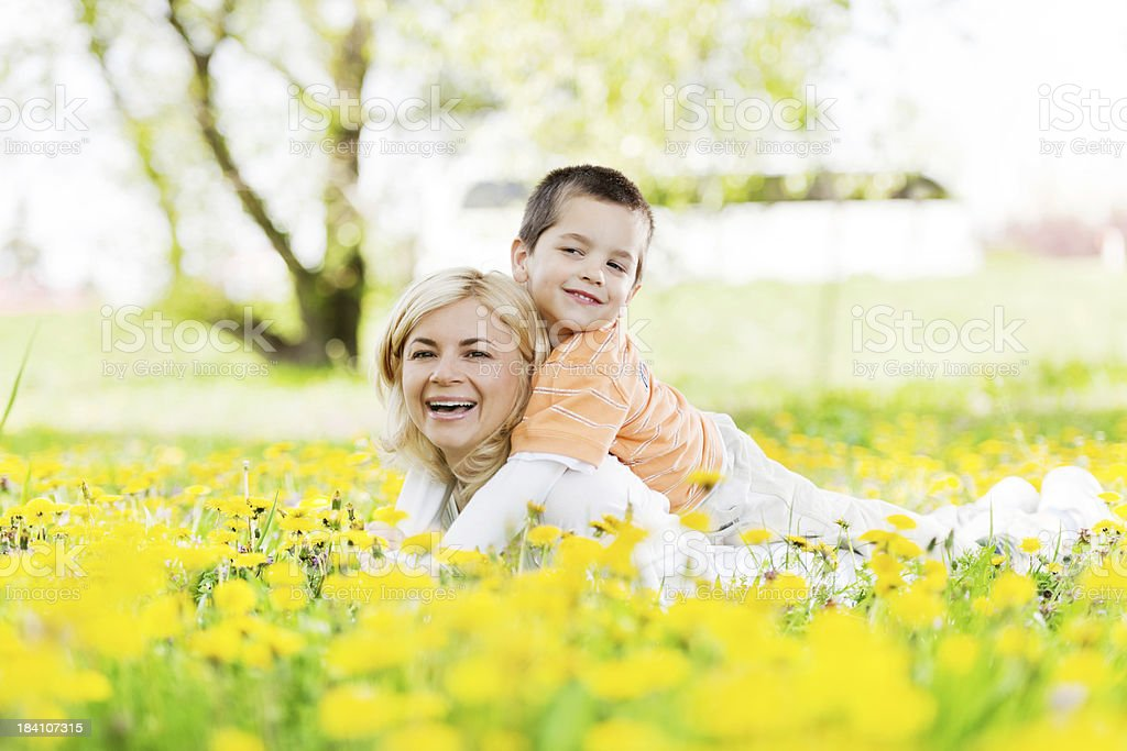 Young mother carrying her son on the piggyback. royalty-free stock photo