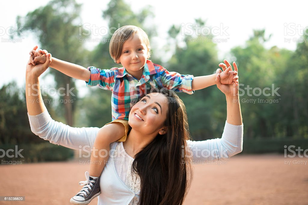 Young mother carrying son and looking up stock photo