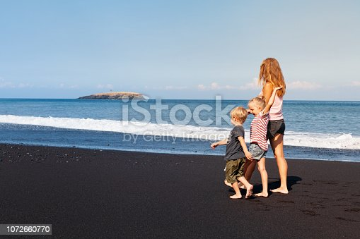 929671306 istock photo Young mother, daughter, son run by black sand beach 1072660770