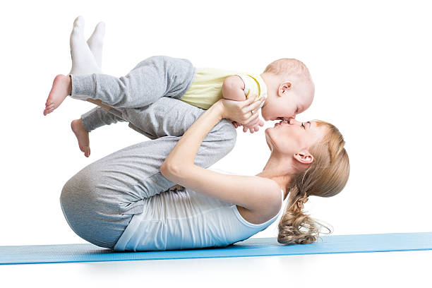 young mother does fitness exercises together with kid boy stock photo