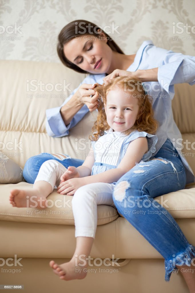 Young mother doing hair of smiling little daughter stock photo