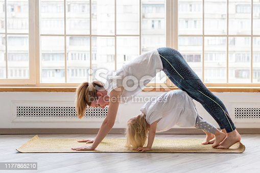 istock Young mother doing yoga with 3-years girl in front of window. Downward facing dog asana 1177865210