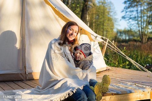 Young mother embracing her 3 years old kid with a blanket while sitting near canvas bell tent in a forest