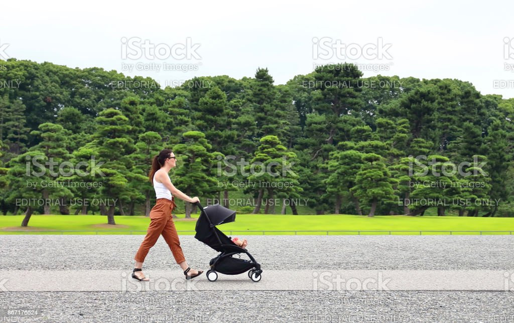 A young mother enjoying the gardens of the imperial palace in Tokyo with her little baby relaxing in his baby carriage stock photo