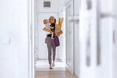 Attractive young woman enters home, holding a grocery bag in one and her baby in another hand. The woman is dressed in black shirt and grey pants and wears a black eyeglasses and a briefcase. Her blonde hair is swept back from her face. Both woman and a baby girl looks happy. The woman could be a single mother coming back from the office. Shallow DOF; Soft focused; Copy space has been left.