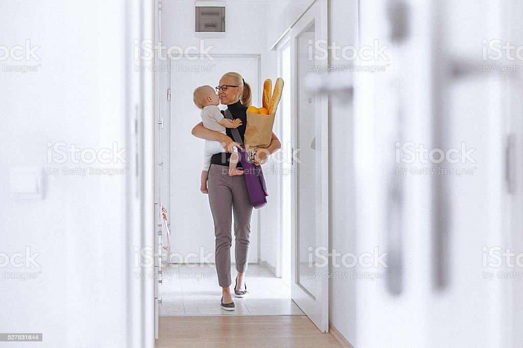 Young mother enters home, carrying her baby and grocery bag stock photo