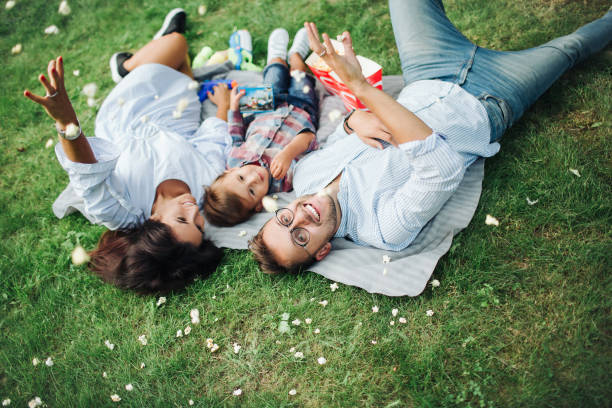 Young mother father baby boy laying on grass in outdoors stock photo
