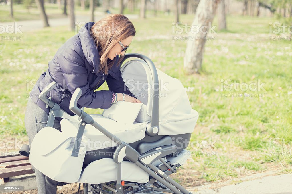 Young mother  feeding baby in the stroller royalty-free stock photo