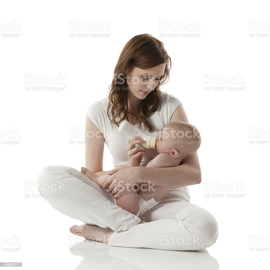 Young mother feeding her baby with milk stock photo
