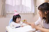 彼女の女の赤ちゃんにヨーグルトを与える若い母