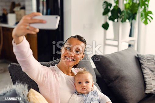 Happy mother and her baby taking selfie with smart phone in the living room.