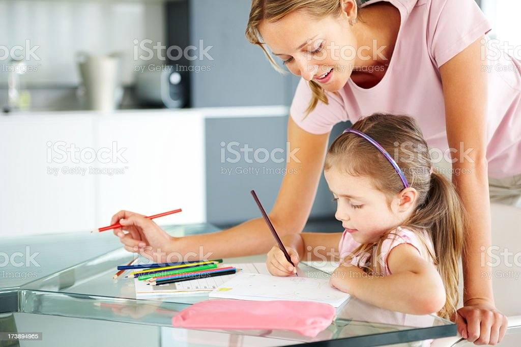 Young mother helping her daughter with schoolwork on a table royalty-free stock photo