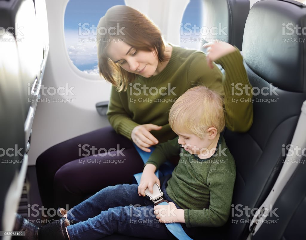 Young mother helping her little son with safety belt during traveling by an airplane stock photo