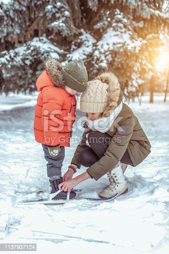 A young mother helps her child, a boy of 4-5 years old, wears clothes for children's skis. First steps in skiing. Support and support, learning healthy lifestyle. In winter, in the city park forest.